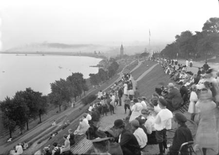 black and white photo of people sitting on the lakefront